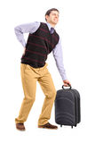 Man lifting his luggage and suffering from a back pain. Full length portrait of a man lifting his luggage and suffering from a back pain  on white background Royalty Free Stock Photo