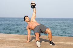 Man lifting kettlebell by the seaside with one arm up Stock Photography
