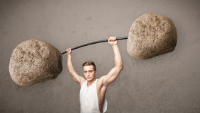 man lifting large rock stone weights Stock Photo