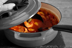 Man lifting lid on a chicken paprika casserole Royalty Free Stock Photo