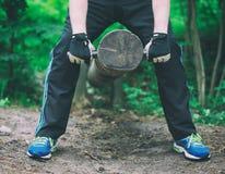 Man lifting log. Stock Images