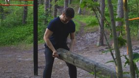 Man lifting log in the forest. Sports concept. stock footage