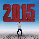Man lifting number 2015 Stock Images
