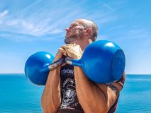 Man Lifting Pair of Blue Kettlebells Stock Photography
