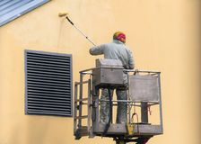Man on a lifting platform painting the building wall with a roller exterior outdoors. Worker on a ladder manually painting yellow. Wall on construction site royalty free stock photos