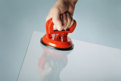Suction Cup. Man lifting a sheet of glass using a vacuum suction cup tool aka dent puller Stock Photography