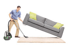 Man lifting a sofa and vacuuming underneath it. Cheerful young man lifting a sofa and cleaning underneath it with vacuum cleaner isolated on white background Stock Photo
