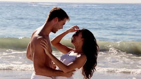 Man lifting up his girlfriend. On a sunny beach during holidays stock video footage
