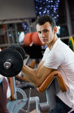 Man lifting weight in a gym Stock Image