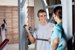 Man Lifting Weights While Looking At Instructor Stock Photo