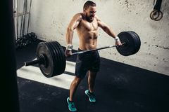 Man lifting weights. muscular man workout in gym doing exercises with barbell. Full length image of tough young man exercising with barbell. Determined male Royalty Free Stock Image
