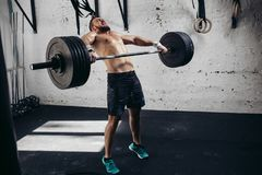 Man lifting weights. muscular man workout in gym doing exercises with barbell. Full length image of tough young man exercising with barbell. Determined male Stock Image