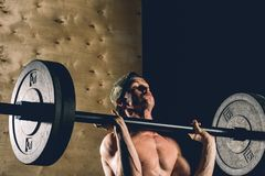 Man lifting weights. muscular man workout in gym doing exercises with barbell stock photography