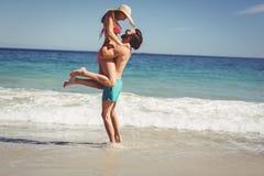 Man lifting woman at beach Stock Image