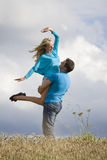 Man lifting woman in countryside Stock Photography