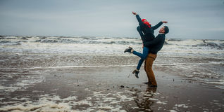 The man lifts the girl in sea water in storm Stock Images