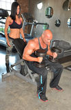 Man Lifts with Spotter. Trainer helps client train with weights. Couple training together Stock Image