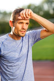 Man in light blue t-shirt wiping sweat after running Stock Images