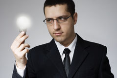 Man with light bulb. A young businessman holding a lit bulb in his hand, looking at it Stock Image