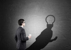 Man with light bulb sketch near blackboard Stock Photography