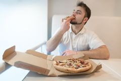 A man in light clothing eats a delicious pizza from a cardboard box. Focus on the cardboard box with pizza. A man in light clothing eats a delicious pizza from Stock Images