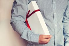 A man in a light shirt holds a white gift box with a red ribbon in his hand. Toning Stock Images
