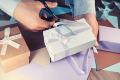 A man in a light shirt is preparing a gift box for the holiday. Toning. Stock Photos