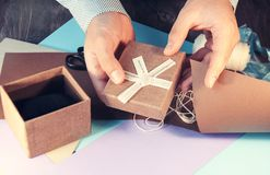A man in a light shirt is preparing a gift box for the holiday. Toning. Stock Photo