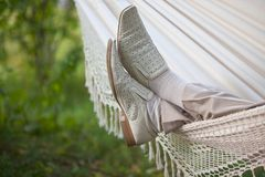 Man in light suit in fabric hammock Stock Image