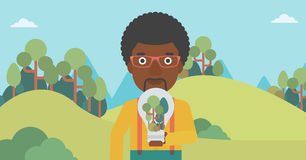 Man with lightbulb and trees inside. Stock Images