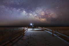 Man lighting a beach path as the Milky Way rises Stock Photo