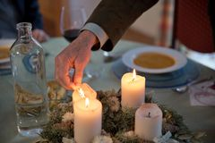 Man lighting the candles on Advent wreath. Person lighting the candles on a richly decorated Advent wreath with a match on a solemnly laid table, ready for a Stock Photos