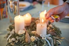 Man lighting candles of Advent wreath. Person lighting the candles on a richly decorated Advent wreath with a match on a solemnly laid table, ready for a festive royalty free stock images