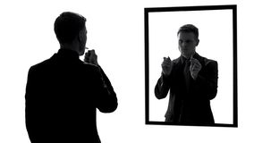 Man lighting cigarette, conscience voice asking quit smoking, mirror reflection. Stock photo stock images