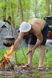 Man lighting a cooking fire while camping Stock Photo