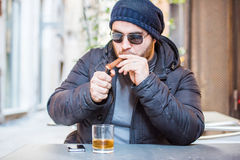 Man lighting a Cuban cigar and drinking whisky Stock Photography
