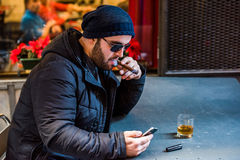 Man lighting a Cuban cigar and drinking whisky Royalty Free Stock Images