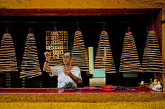 Man lighting incense in chinese temple vietnam Stock Photos