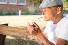 Man lighting up a cannabis joint. Man sitting in a park lighting up a cannabis joint clenched between his teeth with his lighter with copyspace stock photos
