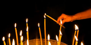 Man lights a candle in the church Royalty Free Stock Photography