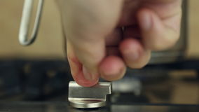 A man lights a gas stove top. He turns a switch and presses it stock footage
