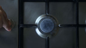 A man lights a gas stove top. He turns a switch and presses it stock video footage