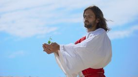 Man like Jesus holding sprout against sky, biblical story of world creation. Stock footage stock footage