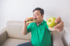 Man likes junk food better than healthy fresh fruit Stock Photography