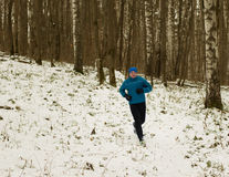 The man likes to run in the winter forest. Royalty Free Stock Photography