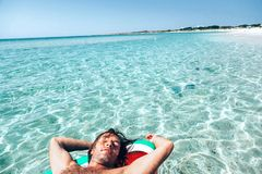 Man on lilo on the beach. Man on lilo in the sea water. Human relaxing on inflatable ring on the beach. Summer vacations Royalty Free Stock Photos