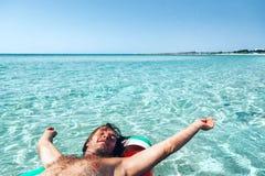 Man on lilo on the beach Stock Image