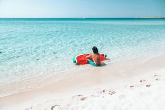 Man on lilo on the beach. Man on lilo in the sea water. Human relaxing on inflatable ring on the beach. Summer vacations Royalty Free Stock Photography