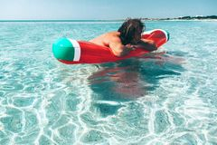 Man on lilo on the beach. Man on lilo in the sea water. Human relaxing on inflatable ring on the beach. Summer vacations Stock Photo