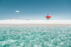 Man on lilo on the beach. Man on lilo in the sea water. Human relaxing on inflatable ring on the beach. Summer vacations, idyllic scene Royalty Free Stock Photos